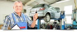 Mechanic holding car keys of a car being worked on in the shop