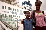 Lisa Moore leaves Mercy Ships with her mother, Teta, the day after her successful cataract surgery on her left eye.  She is given a pair of sun glasses to protect her eyes from the bright sunlight & dusty environmental conditions. They must be worn until Lisa is reviewed at the Mercy Ships eye clinic in Monrovia, 2 weeks after her operation.