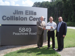 Duke Doubleday presents the certificate to Jim Ellis Collision Center Director Marc Sizemore along with Doc Scheffler