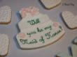 A photo of a vegan sugar cookie in the shape of a wedding cake with customized elements.