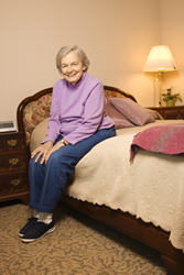 Female senior citizen sitting on adjustable bed in flat position.