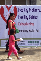 "Mother and girl walk in front of the ""Healthy Mothers Healthy Babies"" sign at a community health fair"
