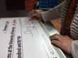 Caring Transitions Owner Lea Nugent signs the check for $1,200 donation.