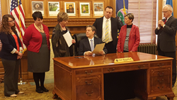 Members of the Kansas Coalition for Problem Gambling watch as Governor Sam Brownback signs a Proclamation commemorating Problem Gambling Awareness Month.