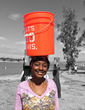 A refugee woman demonstrates how she would carry a heavy bucket of water on her head for long distances.