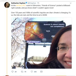 Guest speaker Dr. Katharine Hayhoe poses with Friends of Science billboard at Edmonton IPCC Climate Conference