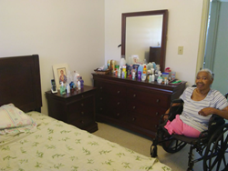 A resident of Flambouyant Gardens shows off the new bedroom set provided through Cane Bay Partners' and Kirk Chewning's donation to Lutheran Social Services.