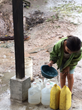 Honduran girl filling water containers.