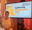 Ascencia Executive Director Natalie Komuro standing in front of the CA Nonprofits Day screen