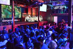 A crowd of students watches an esports game on a giant screen in a large arena.
