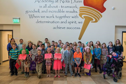 More than 40 elementary students stand in front of their school lobby holding their Great Reading Games award certificates.