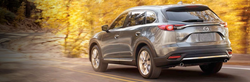 Rear view of gray mazda cx-9 driving by trees with yellow leaves