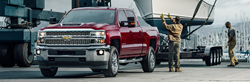 front and side view of red 2019 chevy silverado 1500 towing large trailer