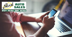 Man using smartphone and laptop with Skook Auto Sales logo in corner