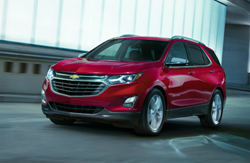 Exterior view of a red 2019 Chevrolet Equinox driving in a parking garage
