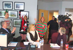 The firm strives to create an environment in which its employees feel happy, accepted and worthy. Photo: News 12 Long Island Crash Caroling at the American Portfolios home office in Holbrook, N.Y.