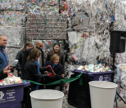 Representatives from FPI, Alpine Waste & Recycling, Denver Public Works, and Sustana cut the ribbon between two purple recycling carts to symbolize Denver's acceptance of paper cups for recycling.