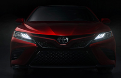 Front View of Red 2019 Toyota Camry with Headlights On