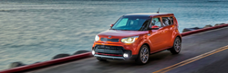 2019 Kia Soul in red driving alongside ocean