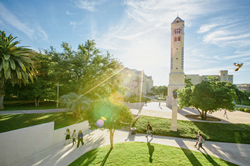 Students walk in front of a bell tower at St. Mary's University.