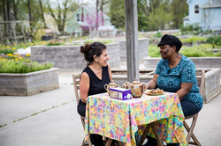Two woman facing each other while sitting at a table set for tea in a park.