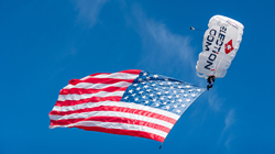 Team Fastrax™  member skydives with a large American flag.