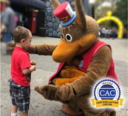 Kennywood Amusement Park mascot Kenny Kangaroo hugs a young guest. Kennywood recently earned the Certified Autism Center designation from the International Board of Credentialing and Continuing Education Standards (IBCCES). A badge announcing this designation is positioned in the lower right corner of the image.