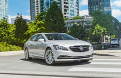 Exterior view of a silver 2018 Buick LaCrosse driving down a city street