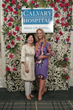 Suzanne Rhow and Joanna Martin posing in front of a flower wall display.