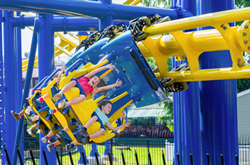 Children with their hands in the air riding a blue and yellow suspended roller coaster