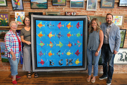 Pictured left to right: Mrs. Martha Besecker, Ms. Andi Finch (The Foundry), Ms. Erika Besecker (Ben Chambers 3rd grade), Mr. Dennis Little (ReliAvail I.T. Company) pose with the quilt at The Foundry's Chambersburg gallery