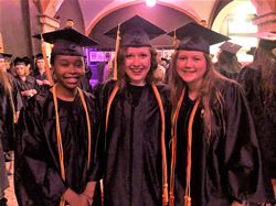 Three female graduates pose together