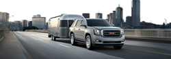 2019 GMC Yukon exterior front fascia and passenger side on blurred highway pulling camper