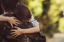 A soldier in a camo jacket hugging a young boy.
