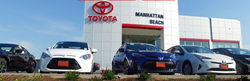an exterior shot of the Manhattan Beach Toyota dealership with a bunch of Corolla and Camry models parked outside