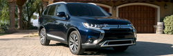 Front passenger view of a dark blue 2019 Mitsubishi Outlander parked outdoors in the sun