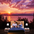 A couple reading and relaxing in bed in natural, evening light, which the NorbSLEEP bulb mimics.