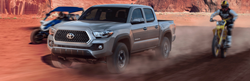 Grey 2019 Toyota Tacoma driving in dirt.