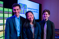 Two male and one female student smiling at camera on stage with National Association for Music Education logo on screen in background.