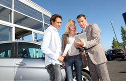 car Salesman with Couple Looking at Papers