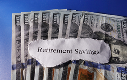 one hundred dollar bills spread out with the text on top of them to say retirement savings