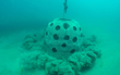 Sand puffs up as one of the 67 structures in the new On Eternal Patrol Memorial Reef is deployed to the ocean floor nine miles off Sarasota.