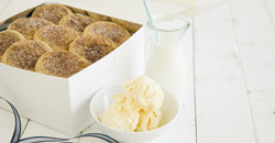 Photo shows an open box of Tiff's Treats' snickerdoodle cookies alongside a glass of milk and a bowl of ice cream.