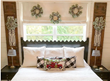 image of holiday guest room bed decorated with wreaths and new bedsheets and white window treatments