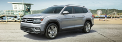 Front driver angle of a white 2019 Volkswagen Atlas with a beach in the background