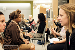 Women sitting in an office space facing each other at an Ellevate event.