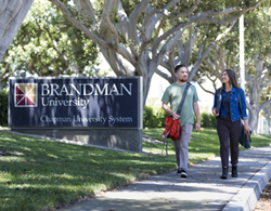 A male student and a female student walk by a Brandman University sign