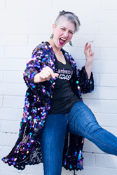 Artist and diversity & inclusion keynote speaker Mallory Whitfield is kicking one leg and reaching one arm towards the camera, smiling. She wears blue jeans, a black tank top, and a purple sequined long jacket.