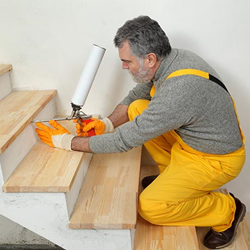 Man putting adhesives on stairs