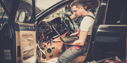 Image of mechanic in vehicle with laptop
